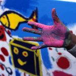 main d'enfant couverte de peinture rose devant une fresque murale