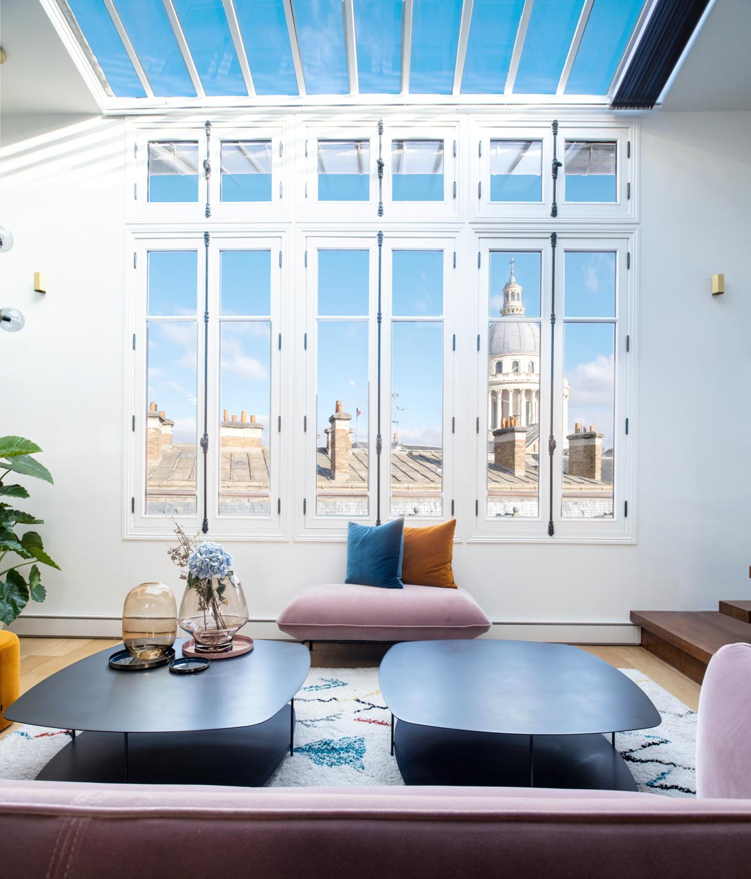 vue sur le Panthéon à paris à travers une verrière qui donne dans un salon, avec un canapé et deux tables basses noires, un pouf avec des coussins