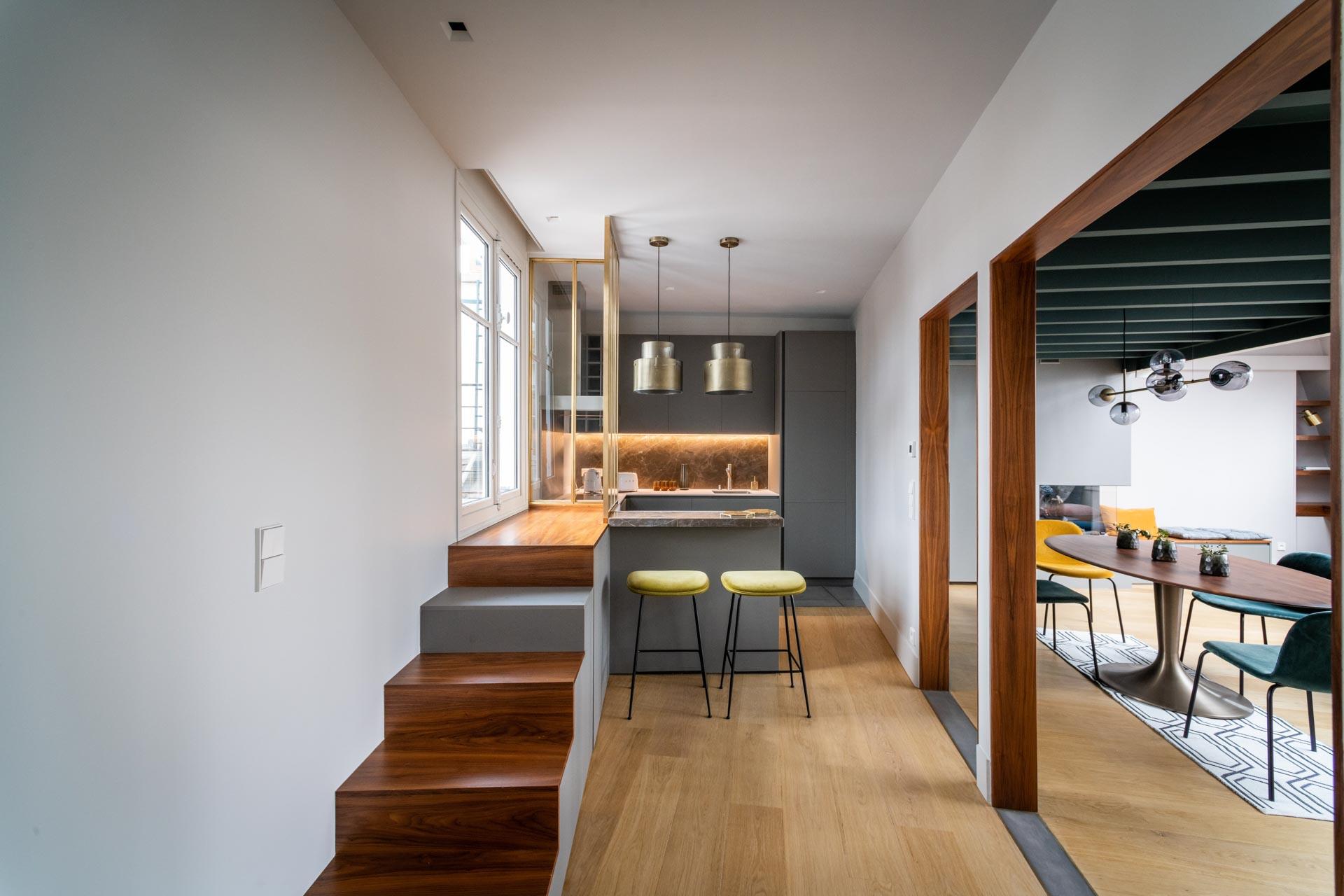 un couloir donne sur une cuisine et une salle à manger avec un escalier vers une fenêtre, plusieurs luminaires au plafond