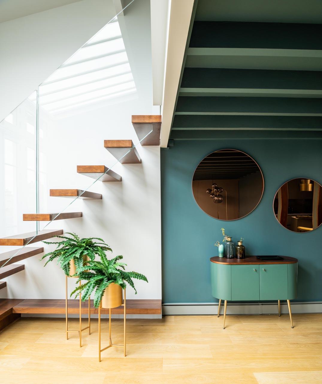 un escalier et une commode avec deux miroirs et des plantes dans deux caches-pots