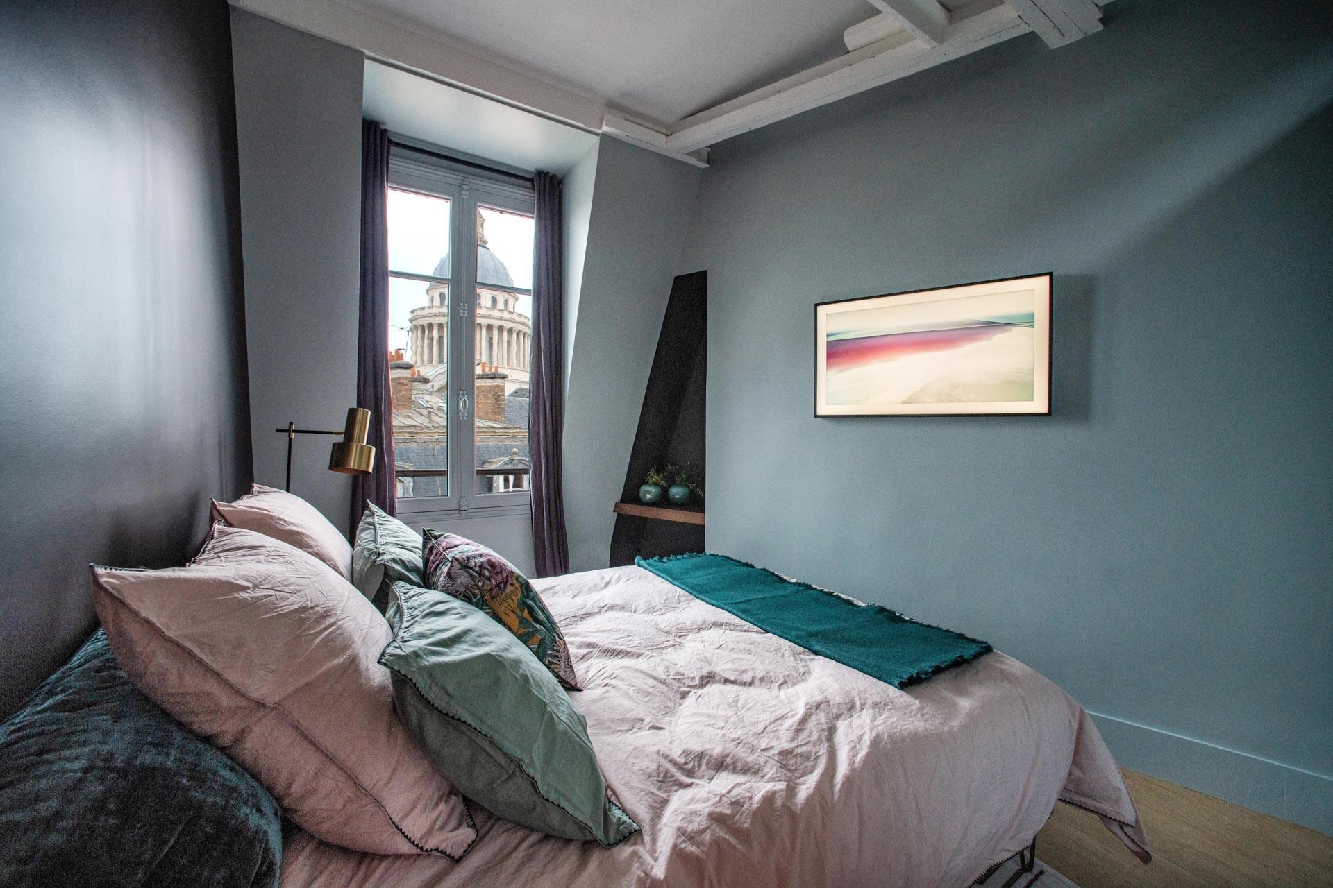 chambre à coucher avec une fenêtre sur le Panthéon, lit avec des draps roses et cinq oreillers