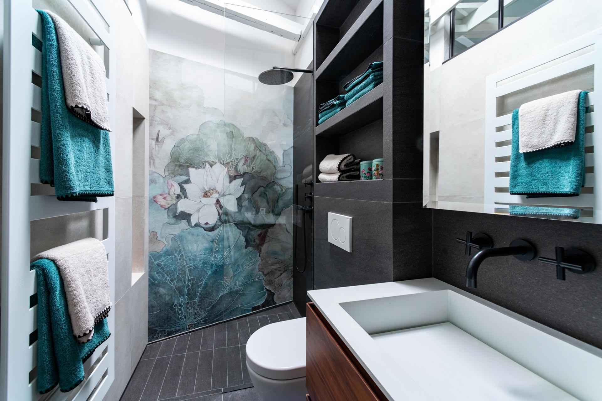 salle de bain avec un lavabo et des wc une douche avec un papier mural représentant un nénuphar